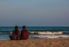 A couple relaxes on the beach Stock Photography