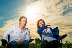 Couple relaxes in chairs and look in the direction Royalty Free Stock Image