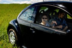 Couple Relaxing. A couple relaxes in their car in an empty field during a road trip Royalty Free Stock Image