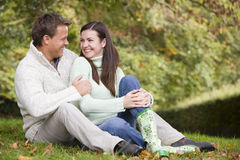 Couple relaxing in autumn woods. Young couple relaxing in autumn woods royalty free stock image