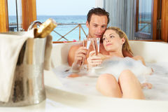 Couple Relaxing In Bath Drinking Champagne Together. Couple Relaxing In Bubble Bath Together Smiling To Each Other Smiling To Camera Royalty Free Stock Photo
