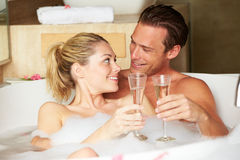 Couple Relaxing In Bath Drinking Champagne Together. Smiling To Camera Stock Photography