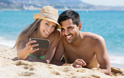 Couple relaxing on beach stock photo