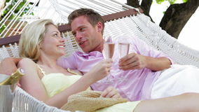 Couple Relaxing In Beach Hammock Drinking Champagne stock video