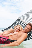 Couple Relaxing In Beach Hammock Stock Photo