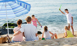 Couple relaxing on beach while their kids playing active games stock images