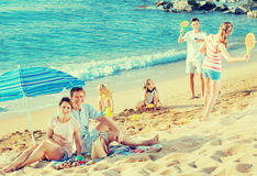 Couple relaxing on beach while their kids playing active games Royalty Free Stock Photo