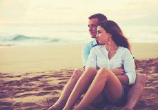 Couple Relaxing on the Beach Watching the Sunset Stock Photography