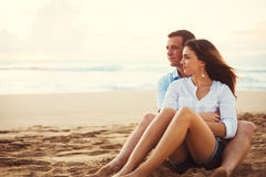 Couple Relaxing on the Beach Watching the Sunset. Happy Young Romantic Couple Relaxing on the Beach Watching the Sunset. Vacation Honeymoon Getaway Royalty Free Stock Photo