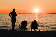 Romantic picnic by the sea. Couple relaxing on the beach while watching the sunset. Romantic evening by the sea. Family vacation Stock Images
