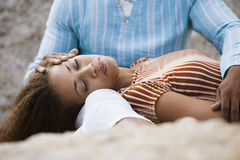 Couple relaxing on beach, woman lying in man's lap, eyes closed, close-up, surface level Stock Photo