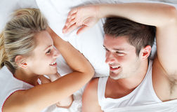 Couple relaxing in bed Stock Images