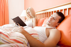 Couple Relaxing in Bed. View of couple in bed, with woman reading book and man sleeping. Horizontal format Royalty Free Stock Photo