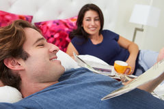 Couple Relaxing In Bed With Coffee And Newspaper Stock Photo