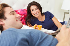 Couple Relaxing In Bed With Coffee And Newspaper Royalty Free Stock Photo
