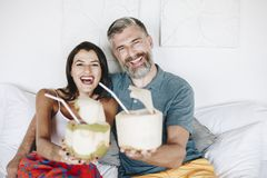 Couple relaxing on the bed drinking coconut stock images