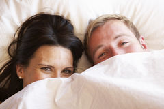 Couple Relaxing In Bed Hiding Under Bedclothes Stock Photo