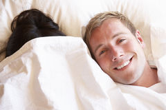 Couple Relaxing In Bed Hiding Under Bedclothes Stock Image