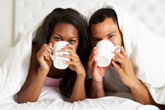 Couple Relaxing In Bed With Hot Drink royalty free stock images