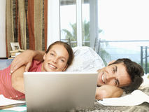Couple relaxing on bed in hotel room, using laptop, smiling, portrait Stock Photography