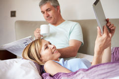 Couple Relaxing In Bed With Newspaper And Digital Tablet Royalty Free Stock Photography