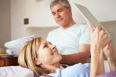 Couple Relaxing In Bed With Newspaper And Digital Tablet Stock Photography