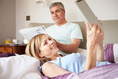 Couple Relaxing In Bed With Newspaper And Digital Tablet Royalty Free Stock Image