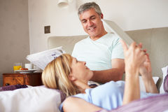 Couple Relaxing In Bed With Newspaper And Digital Tablet Stock Photos