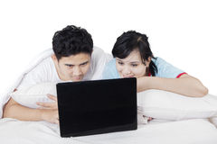 Couple relaxing on bed while using laptop Royalty Free Stock Images