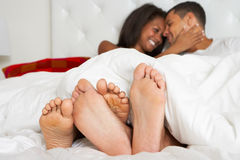 Couple Relaxing In Bed Wearing Pajamas Stock Photos