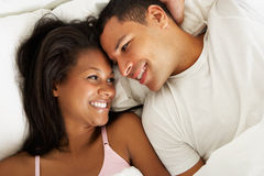 Couple Relaxing In Bed Wearing Pajamas Royalty Free Stock Images