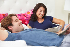 Couple Relaxing In Bed Wearing Pajamas And Reading Newspaper Stock Image