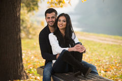 Couple Relaxing On Bench In Autumn Park stock photography