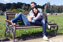Couple relaxing on bench in front of skyline summer time. Royalty Free Stock Photography