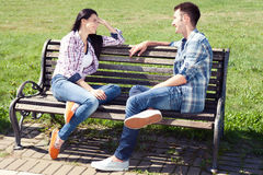 Couple relaxing on bench in front of skyline summer time. Stock Photo