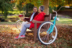 Couple relaxing on bench at park royalty free stock photo