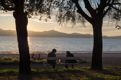 Couple relaxing on a bench during the sunset