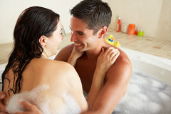 Couple Relaxing In Bubble Filled Bath. Smiling Royalty Free Stock Photos