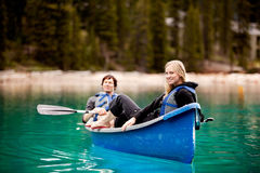 Couple Relaxing in a Canoe. A happy couple relaxing in a canoe on a glacial lake royalty free stock image