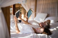 Couple relaxing on canopy bed Stock Photo