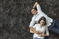 Couple relaxing on the carpet Stock Image