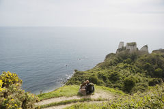 Couple Relaxing On Cliff Looking At Ocean View Stock Photo