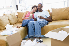 Couple relaxing with coffee by boxes in new home Royalty Free Stock Photo