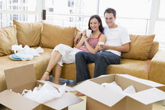 Couple relaxing with coffee by boxes in new home royalty free stock photography
