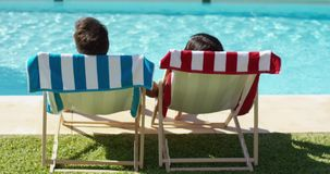 Couple relaxing in colorful deck chairs poolside stock footage