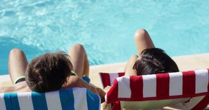 Couple relaxing in colorful deck chairs poolside stock video footage
