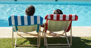 Couple relaxing in colorful deck chairs poolside Stock Photos