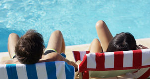 Couple relaxing in colorful deck chairs poolside Stock Images