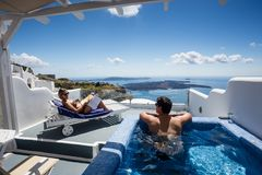 Couple relaxing and contemplating beautiful scene from private pool in one of Oia, Santorini, Greece.  stock image