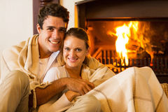 Couple relaxing couch. Happy couple relaxing on the couch next to fireplace Stock Photos